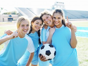 Smiling Female Soccer Players Holding Soccer